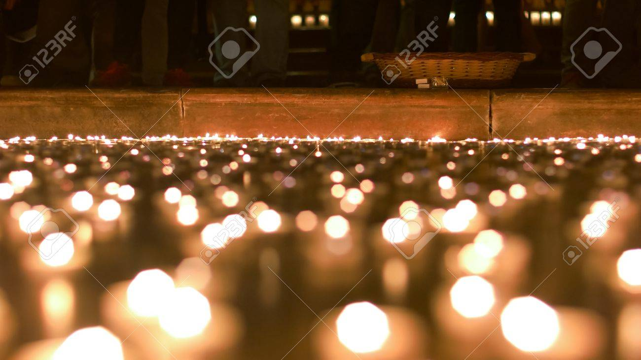 Candles lit by people burning in front of the church podium - 60533724
