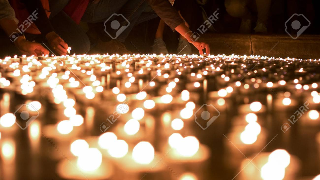Few people saying their blessings and placing the candles on the ground - 60533730