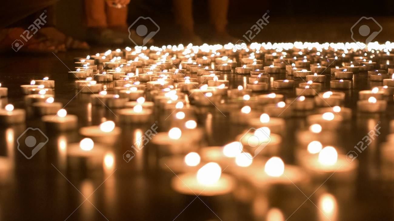 Religious adult caucasian man placing burning candle on the ground - 60533731