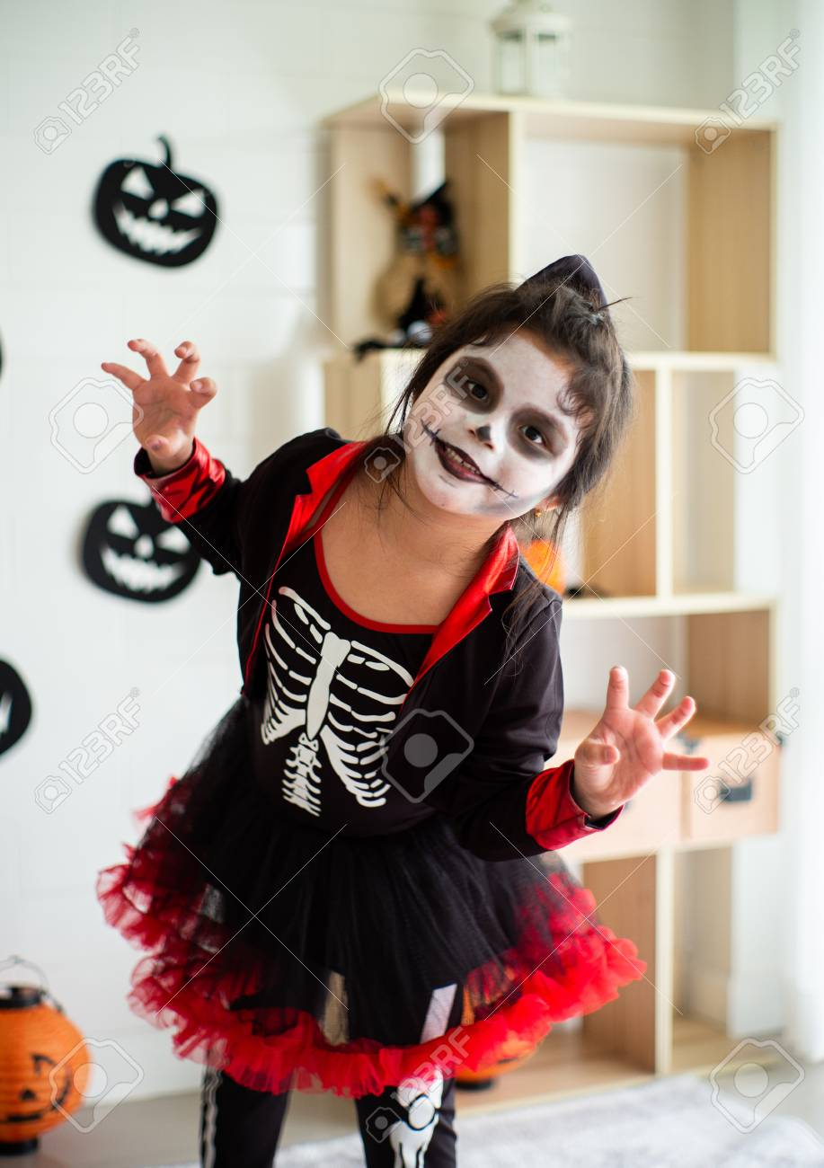 portrait asian little girl in halloween costume acting scary.. stock