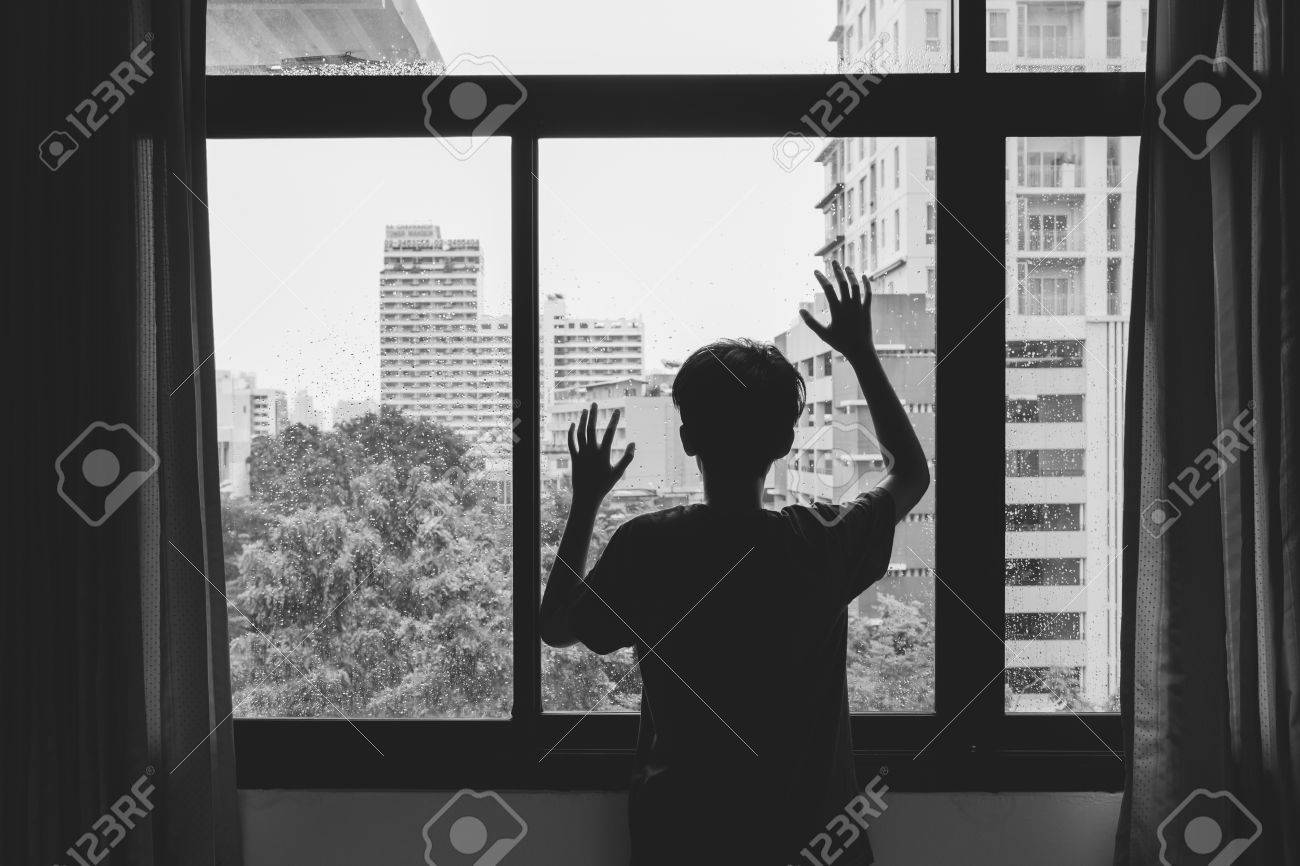 Someone standing by window with raindrops on a rainy day - 45127772
