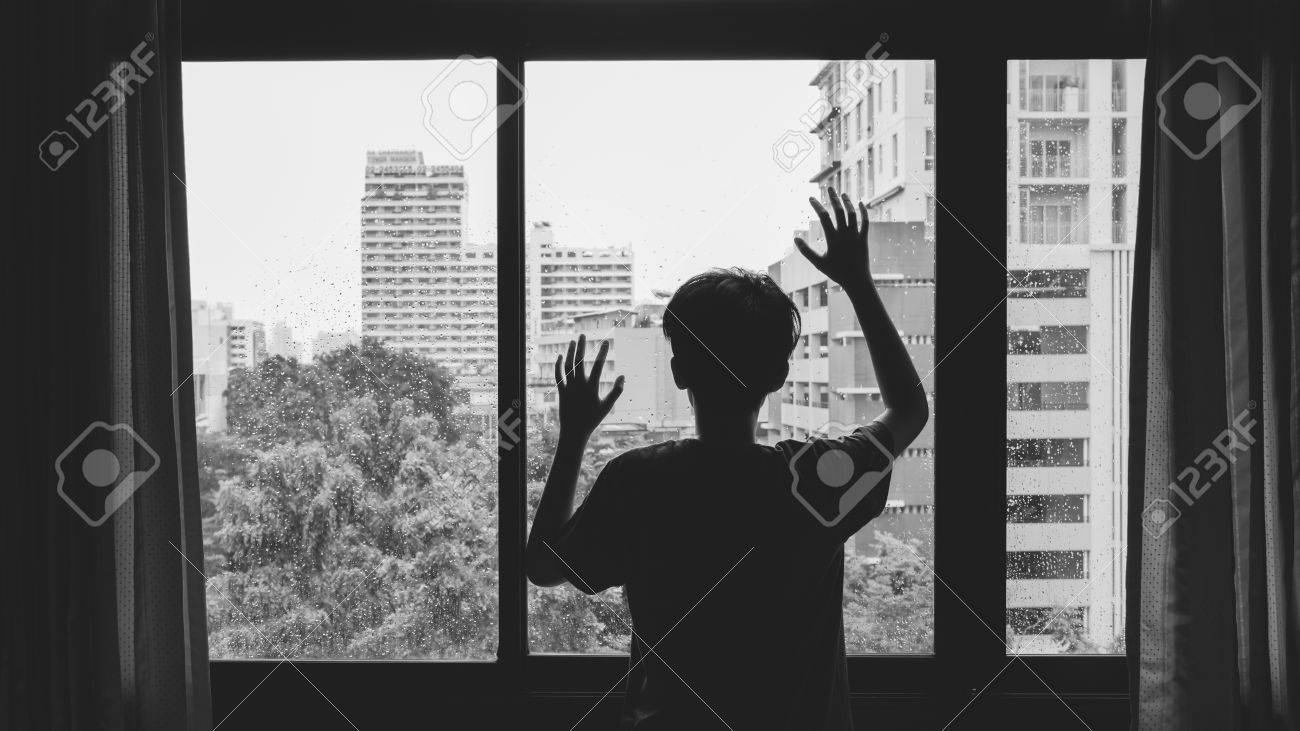 Someone standing by window with raindrops on a rainy day - 45127775