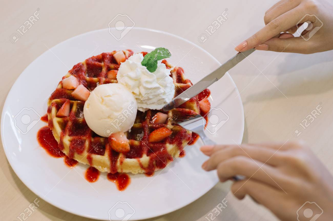 Belgian waffles with ice cream and strawberries ,Hand preparing to eat. - 60536114