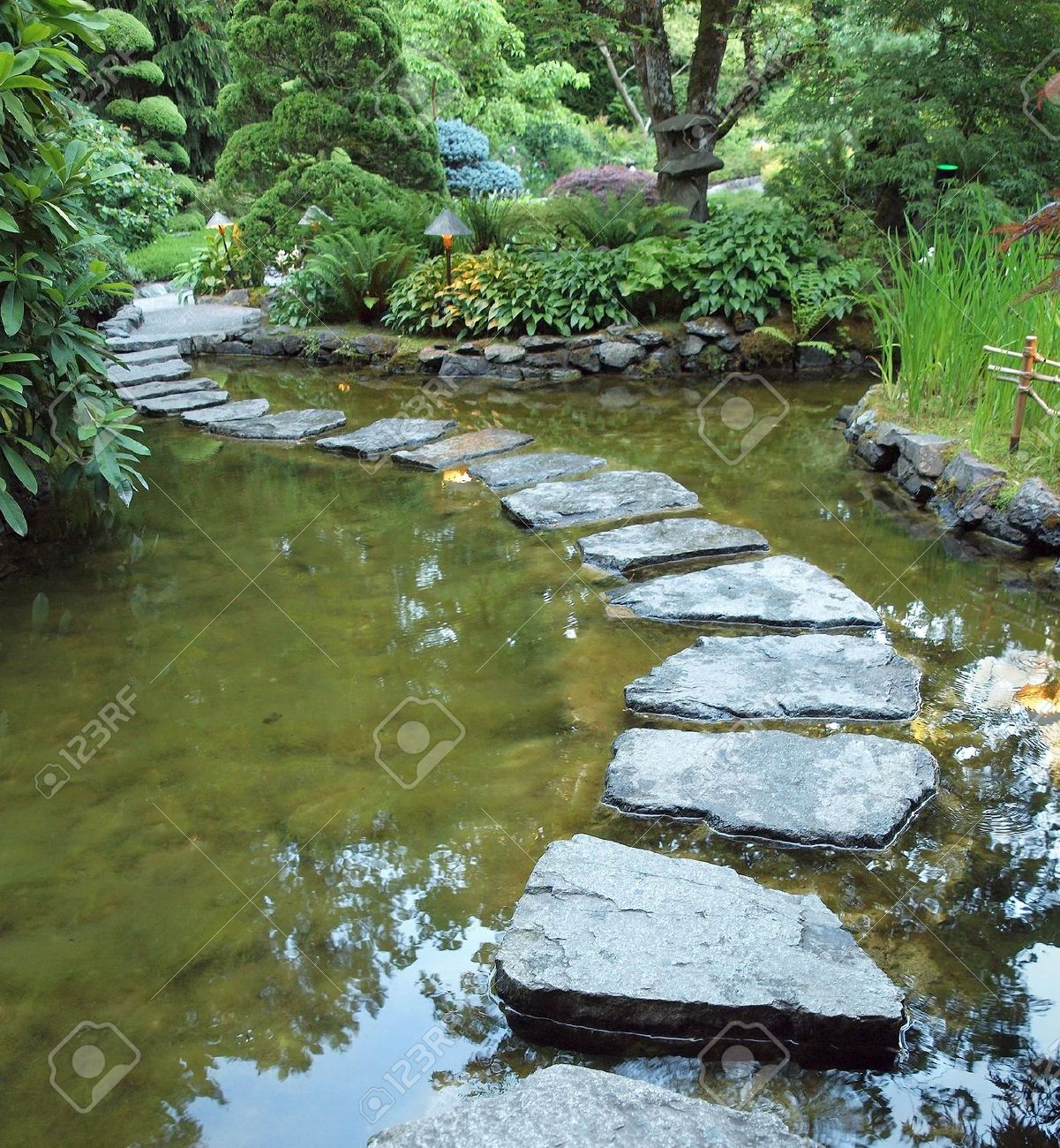 stepping stones form walking path over the pond at night stock