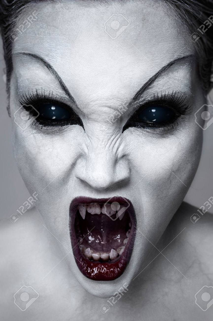 Close up portrait of a screaming undead girl with sharp teeth white skin and black