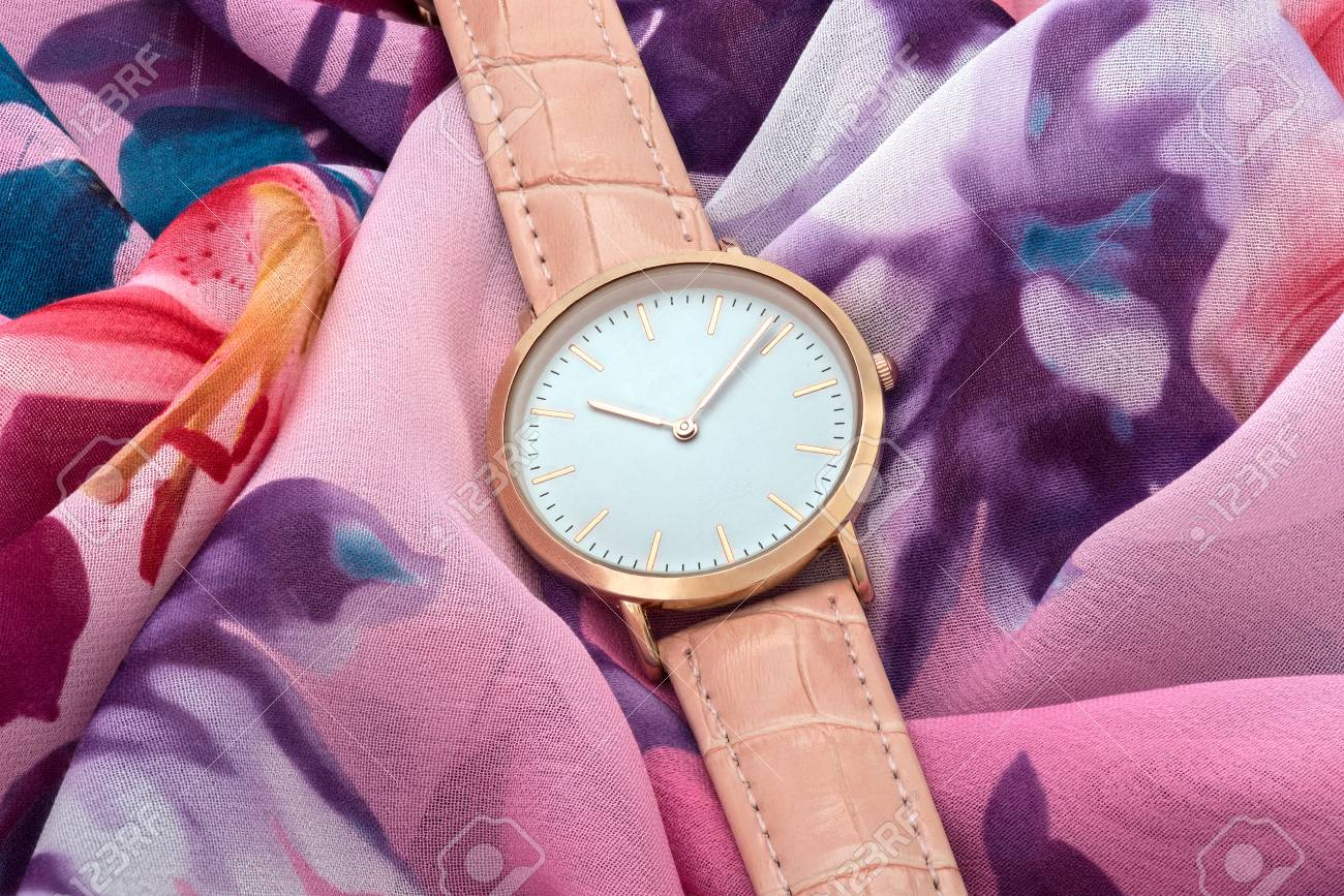 Classic pink wrist watch on colourful silk fabric background - 70001498