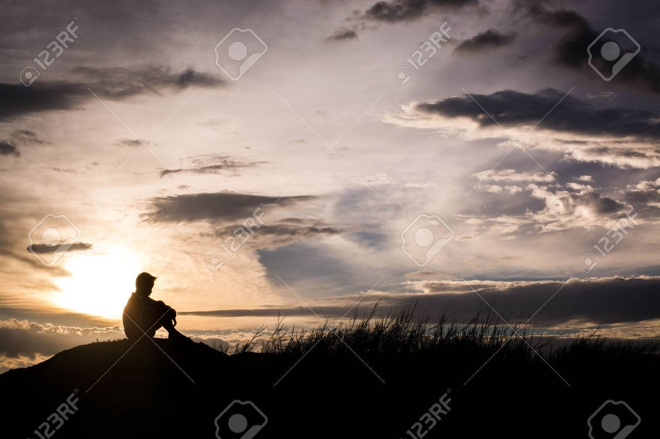 Sad boy silhouette worried on the meadow at sunset silhouette concept stock photo 57330243