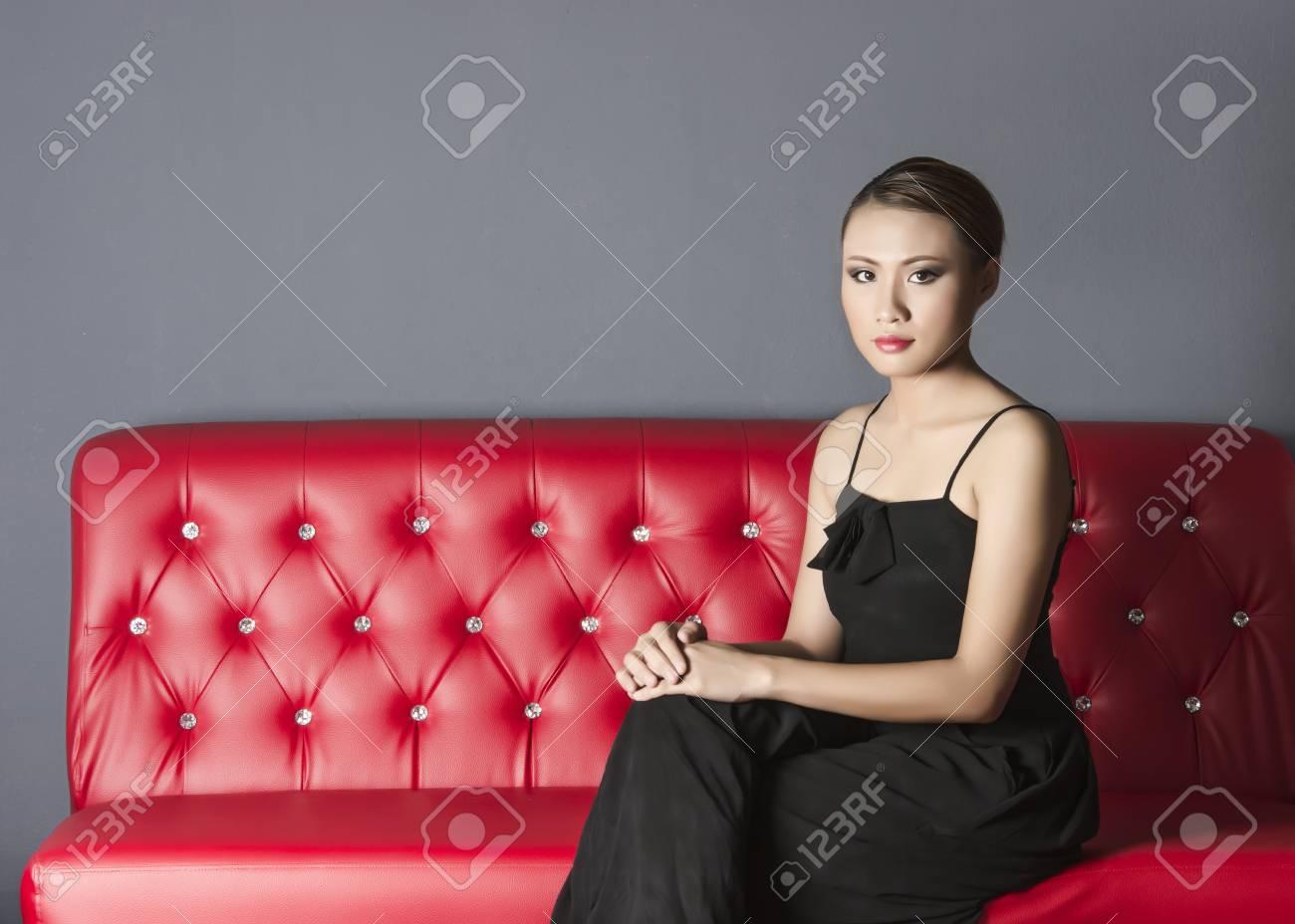 Beautiful woman in black dress sitting on red sofa