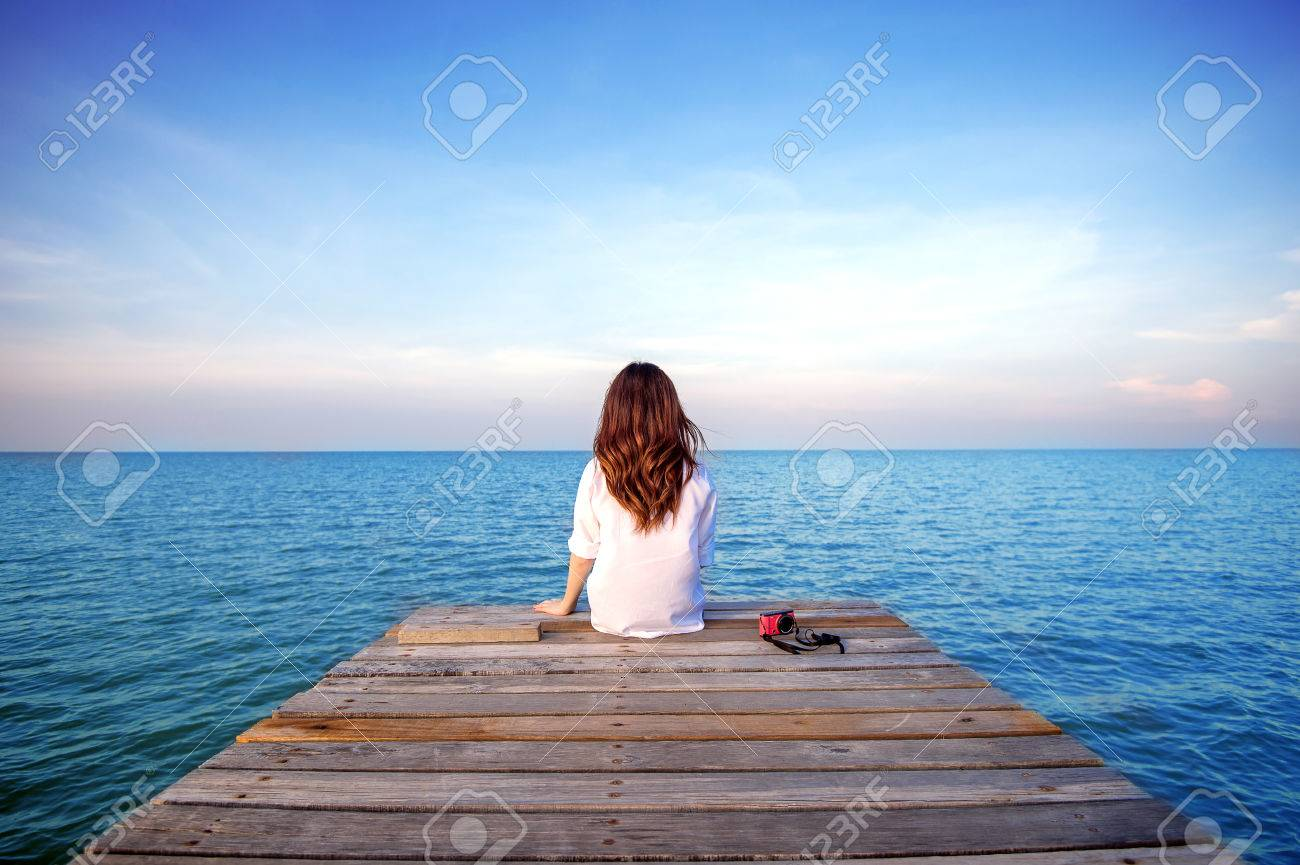 Girl Sitting Alone On A The Wooden Bridge On The Sea. (frustrated ...