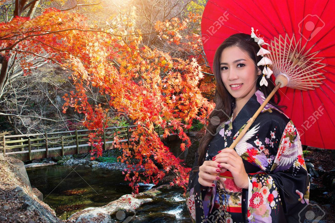 3e3b3aa24636e Asian woman wearing traditional japanese kimono with red umbrella in autumn.  Stock Photo - 81342913