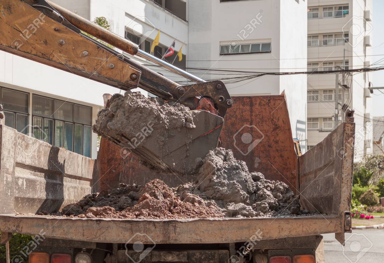 Excavator or soil, mud into truck body, Work in day with sunlight