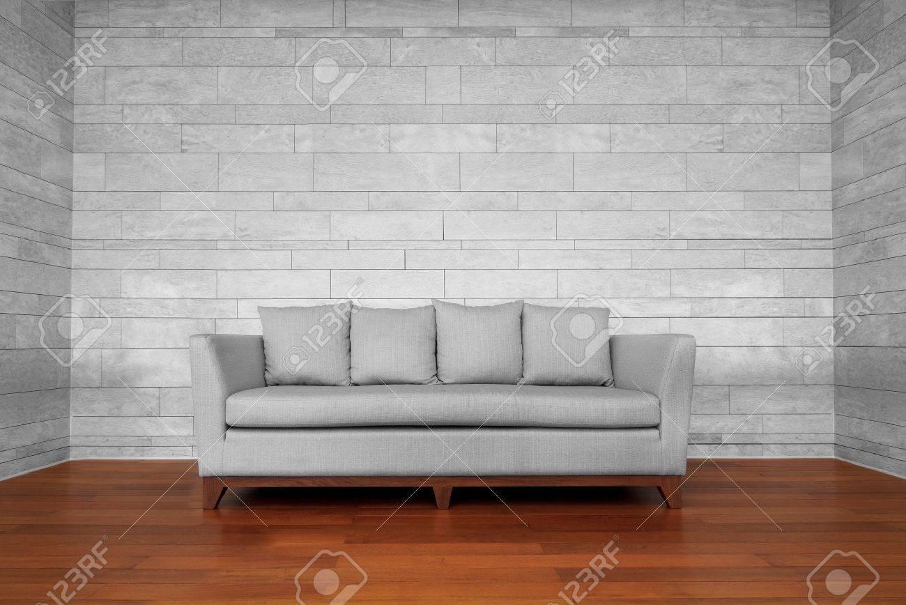 Grau couch stuhl auf braunen hölzernen fußboden und weiße wand ...