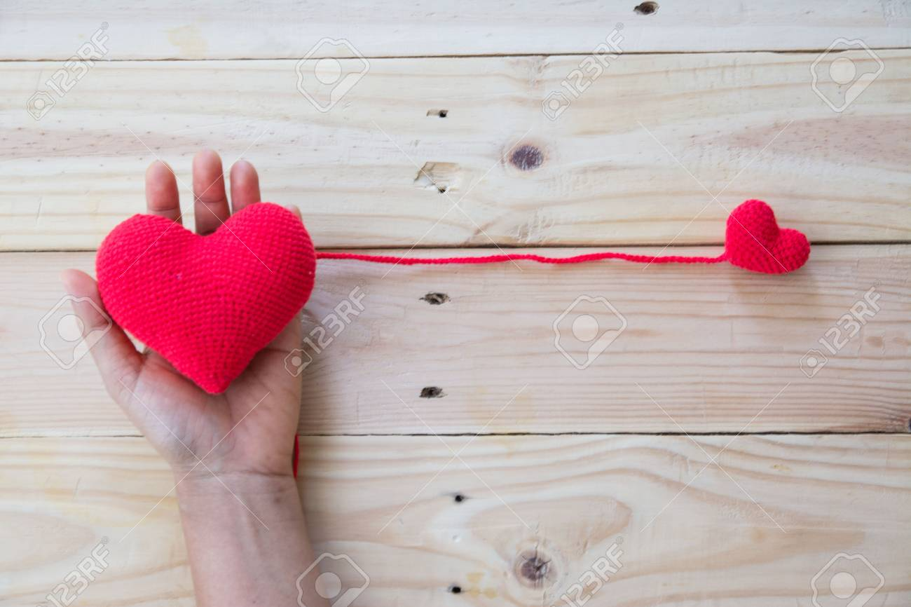Hand Holding Red Heart Crochet Knit Of Yarn On Wood Background