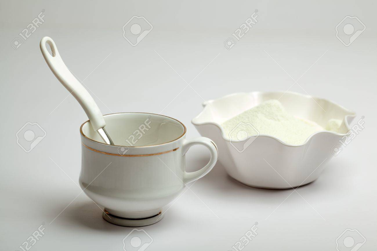 White cup, spoon and milk powder isolated over white Stock Photo - 16080288