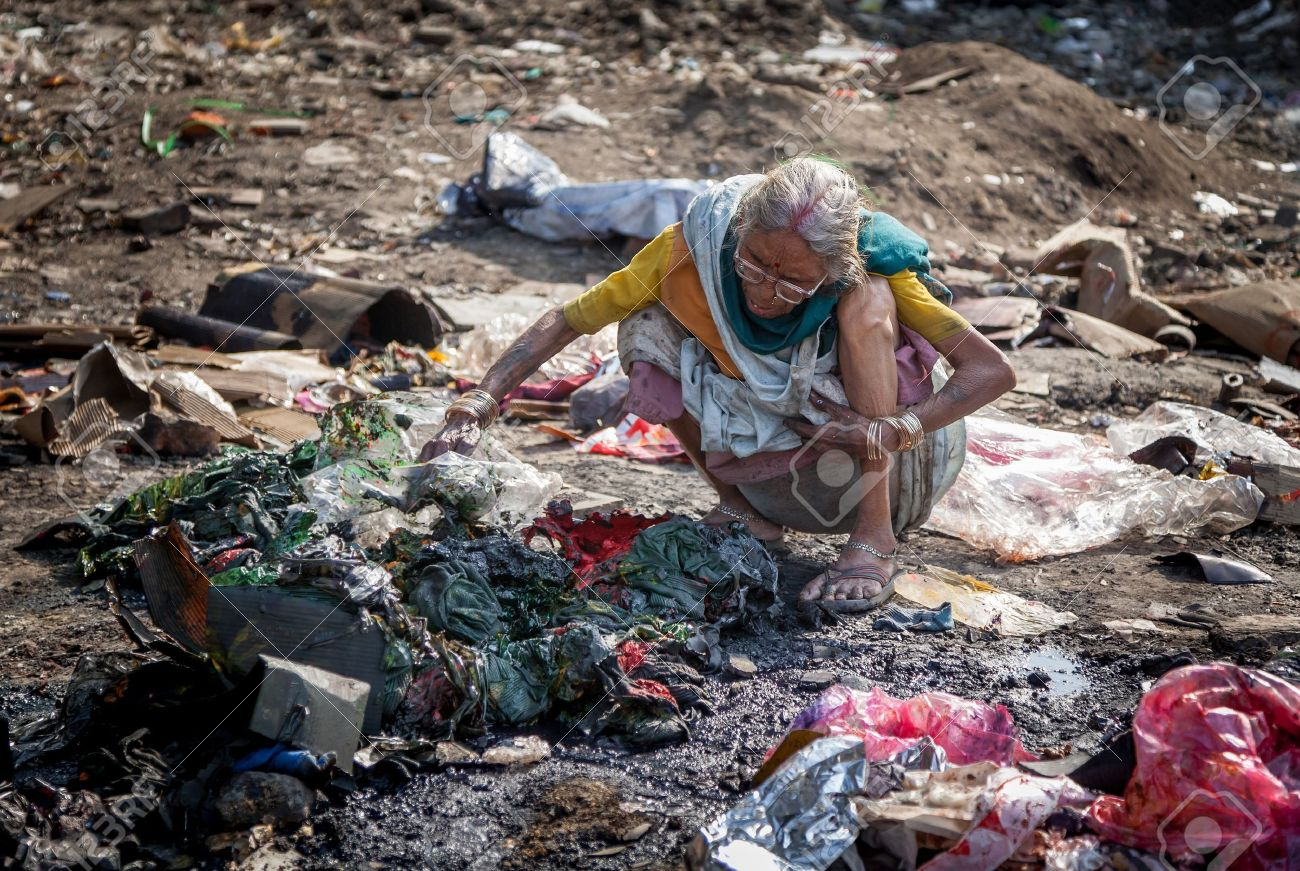 Pollution and poverty   Indian old female sitting  for warmup  herself near fire  in  garbage, Stock Photo - 18264352