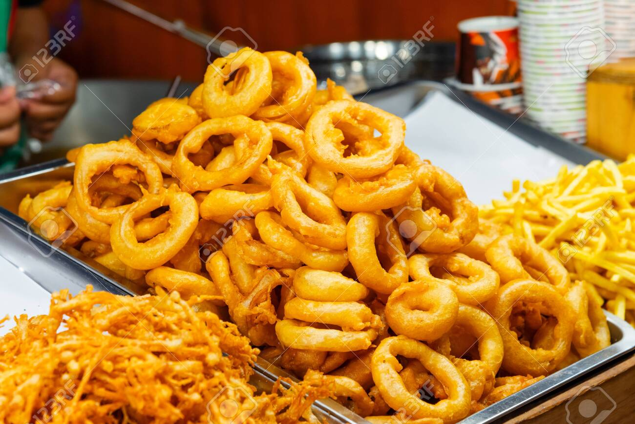 Golden crunchy homemade fried onion rings on tray at street food market of Thailand - 137077482