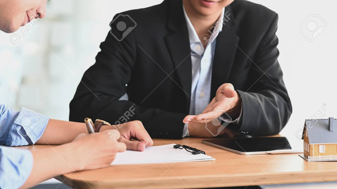 Cropped shot of Real estate agent offer house insurance or house ownership to smart man in blue shirt at the modern wooden table. Signing on agreement, Broker/Seller/Dealer concept. - 141268009