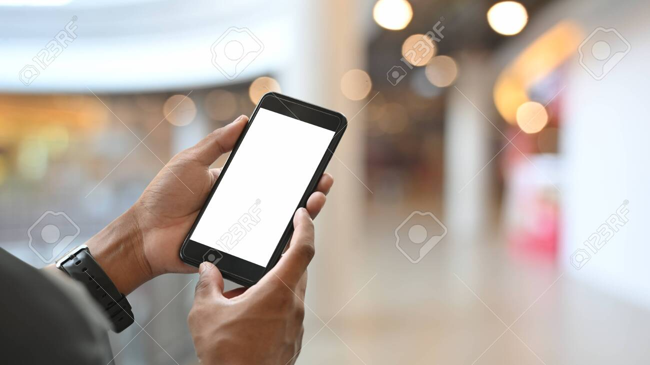 Cropped shot of young businessman holding crop black smartphone with white blank screen on hands while walking at the shopping center with blurred background. - 141363145