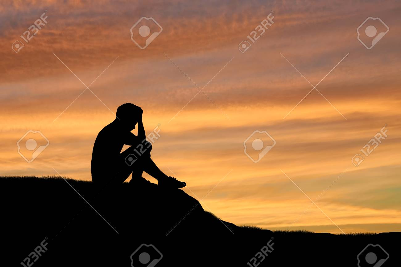 Silhouette of a crying lonely boy on a sunset background stock
