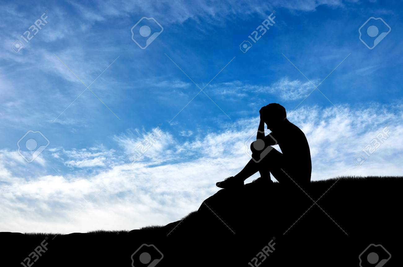 Silhouette of a crying lonely boy against sky stock photo