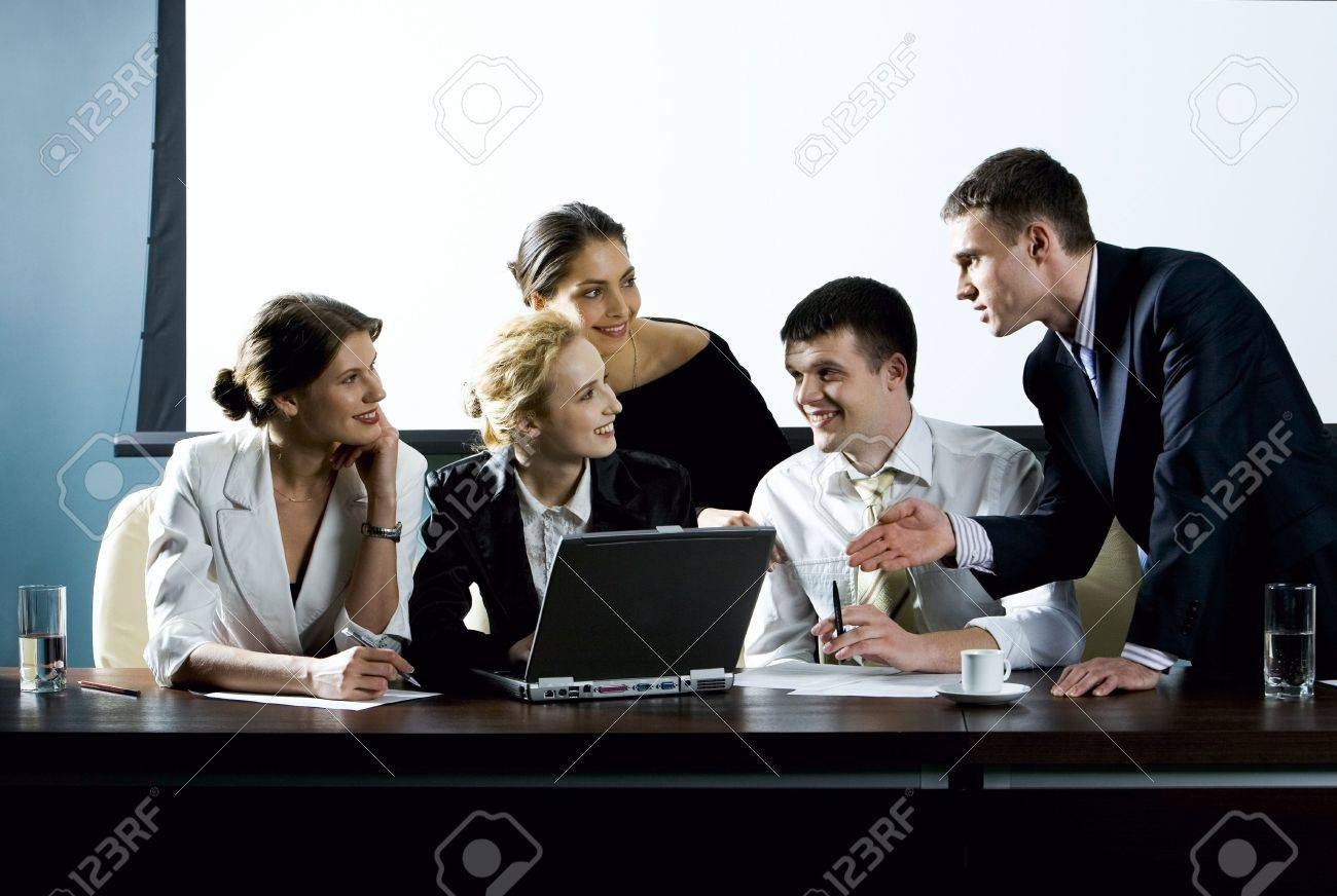 Large group of young businessman gathered together around the laptop discussing interesting question Stock Photo - 1281796