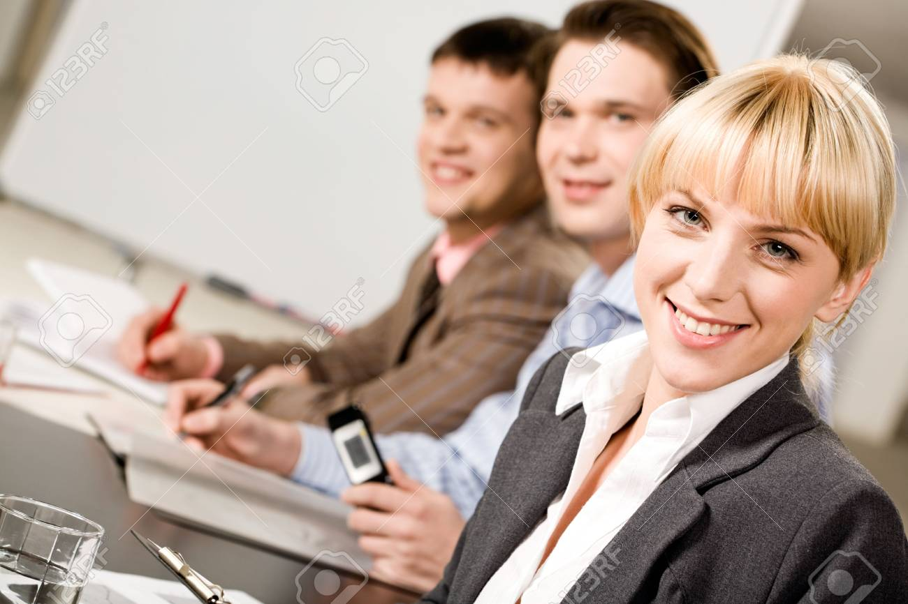 Portrait of pretty employee looking at camera on the background of business men Stock Photo - 2432361