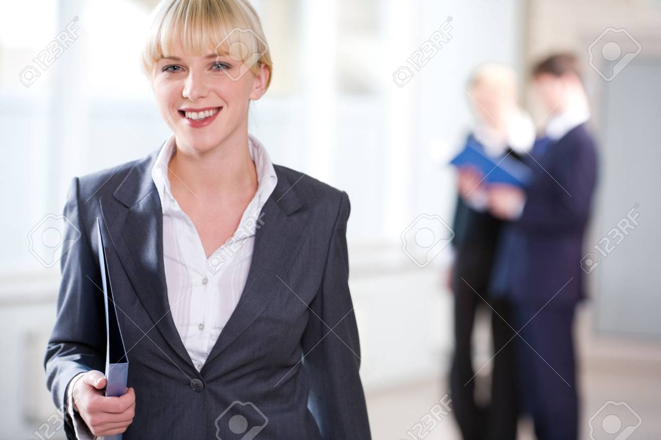 Portrait of young business woman holding a folder on the background of people Stock Photo - 2464107
