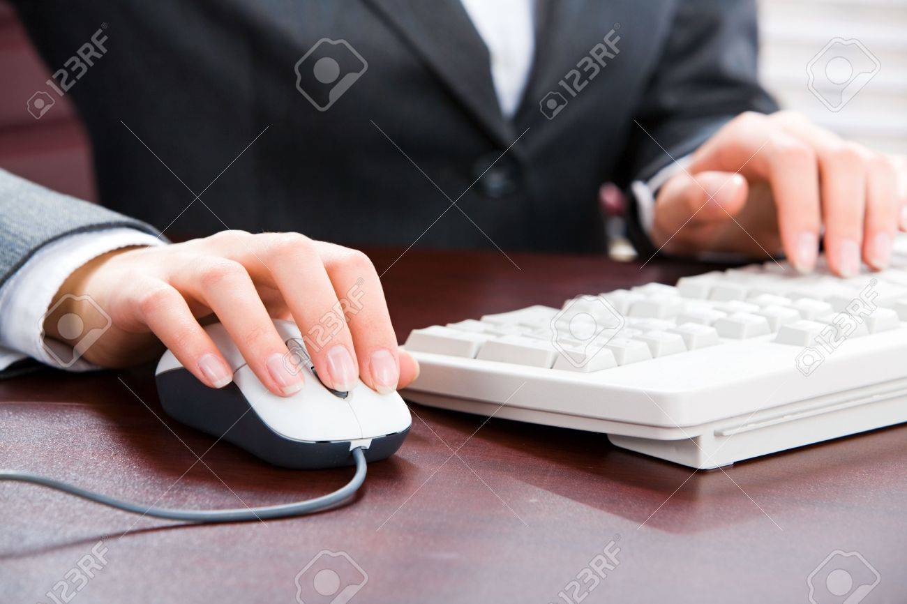 Business woman�s hands touching computer mouse and white keyboard Stock Photo - 2464876
