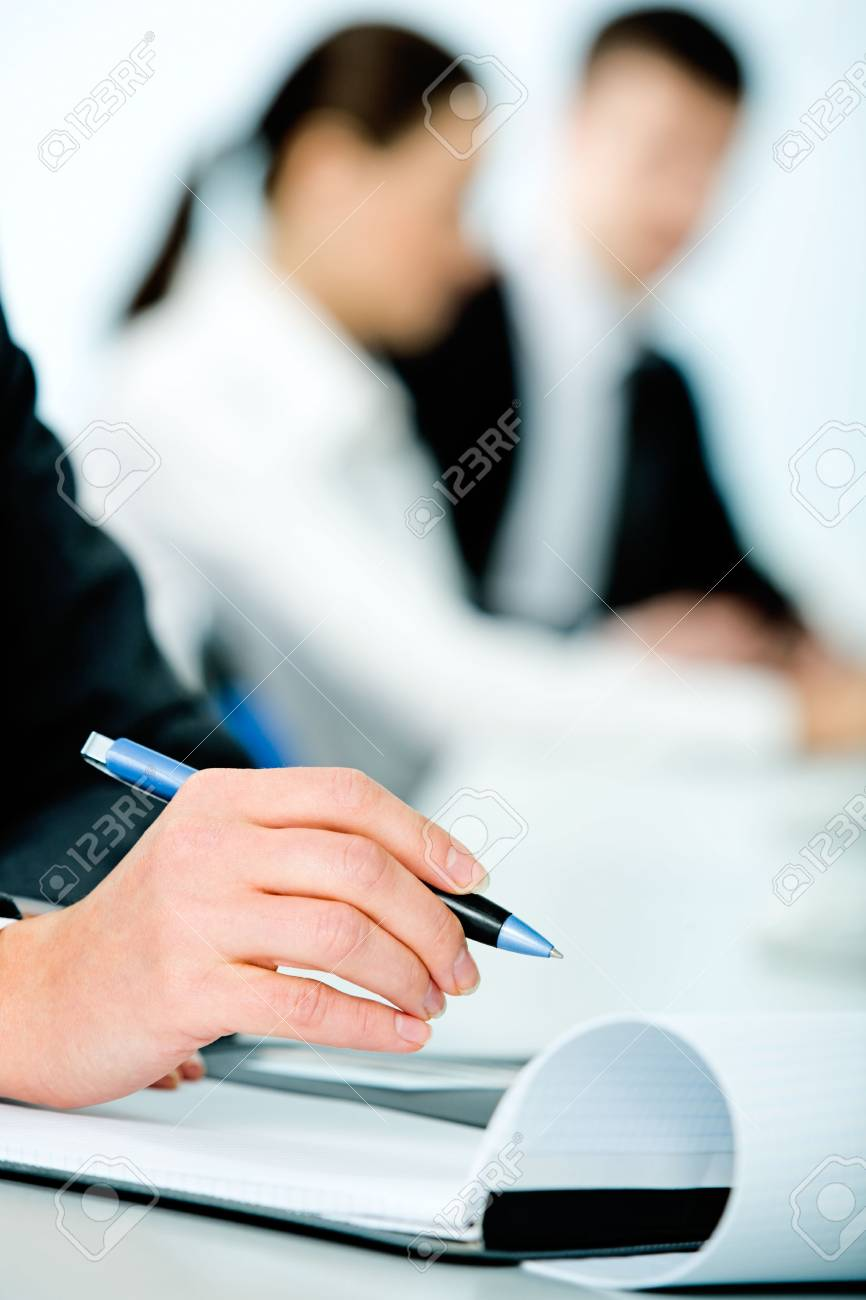 Close-up of woman�s hand holding a pen on the background of people Stock Photo - 2567258
