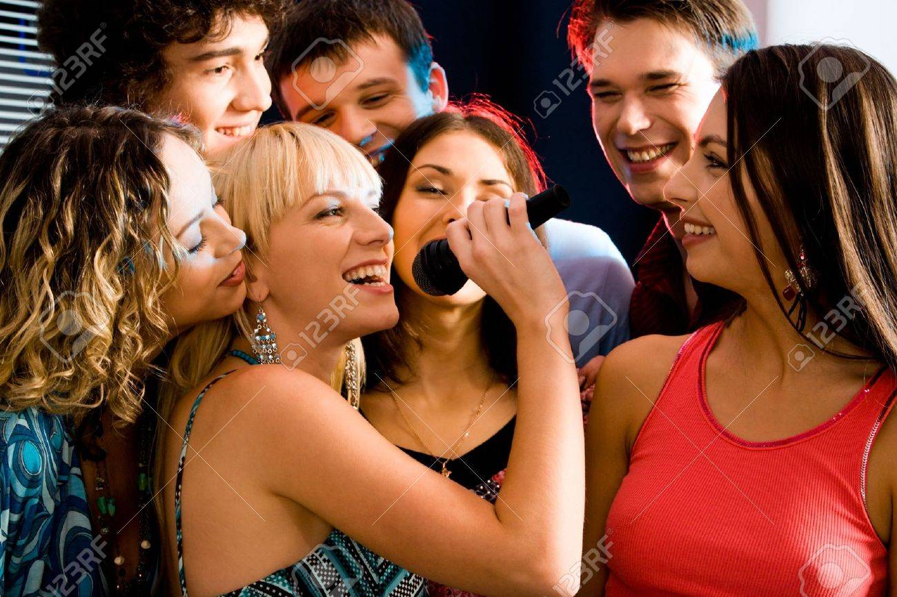 Pretty woman sings a song in the environment of her friends at a karaoke party Stock Photo - 2644788