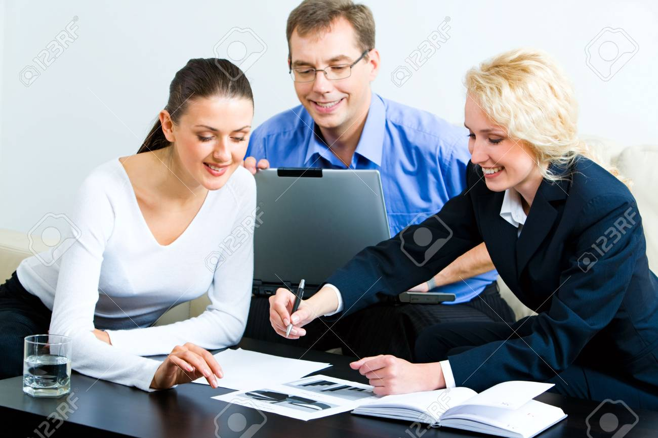 Image of three sitting colleagues looking at graph on the table with notebook, glass of water and some documents near by Stock Photo - 2709558