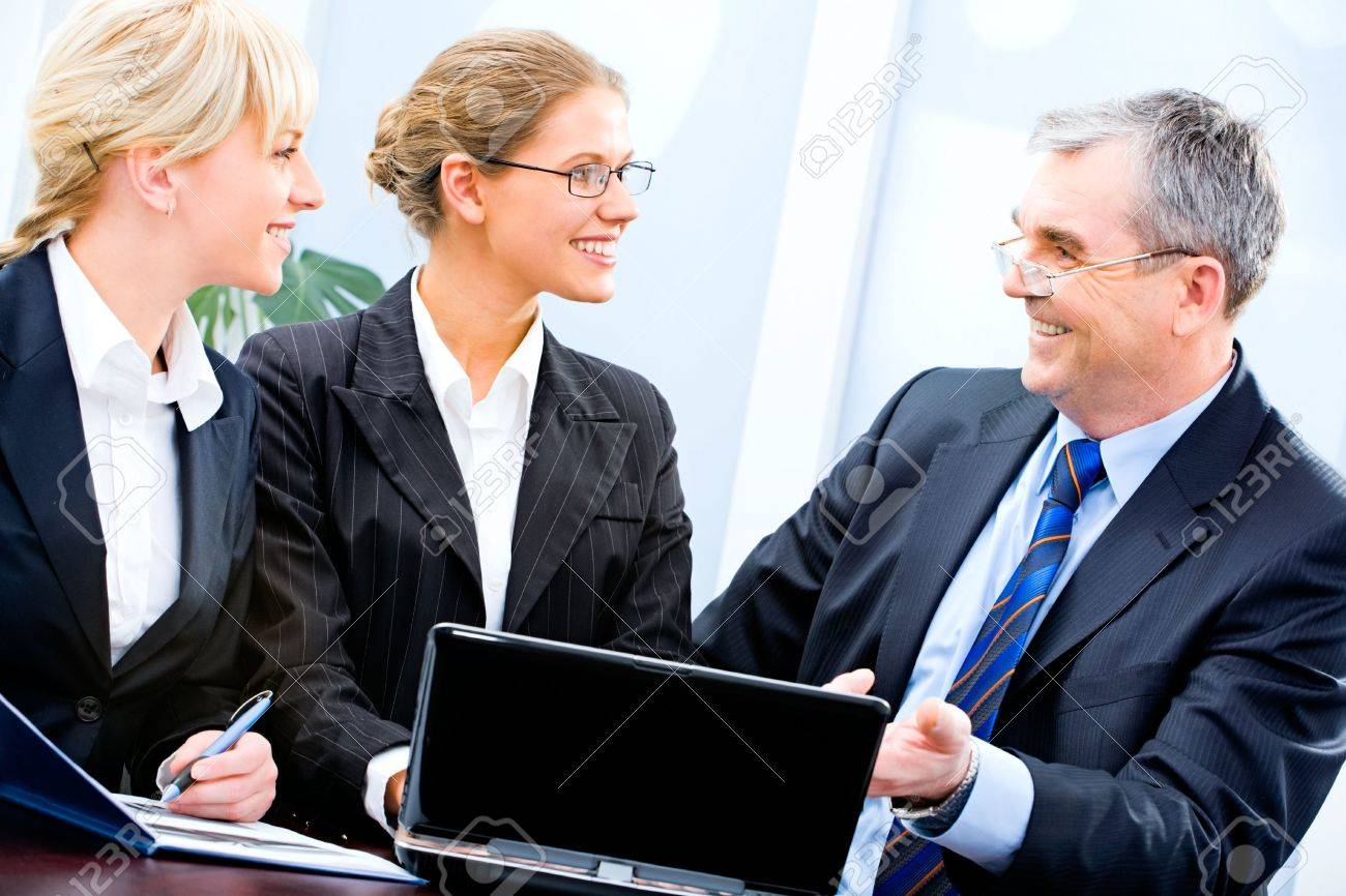 Portrait of three businesspeople sitting near laptop and discussing working ideas in the office Stock Photo - 2752203