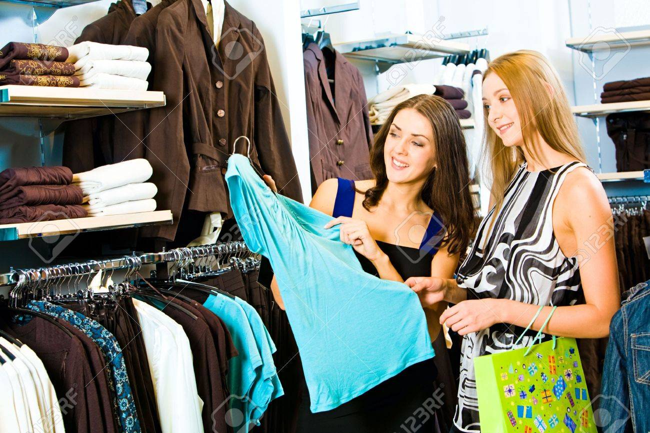 9573d836b136 Photo Of Two Girls In The Clothing Store Holding A Blue Dress ...