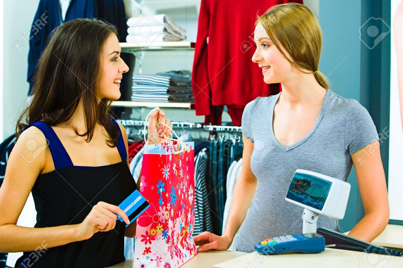 portrait of a buyer and a shop assistant looking at each other portrait of a buyer and a shop assistant looking at each other smiles by the