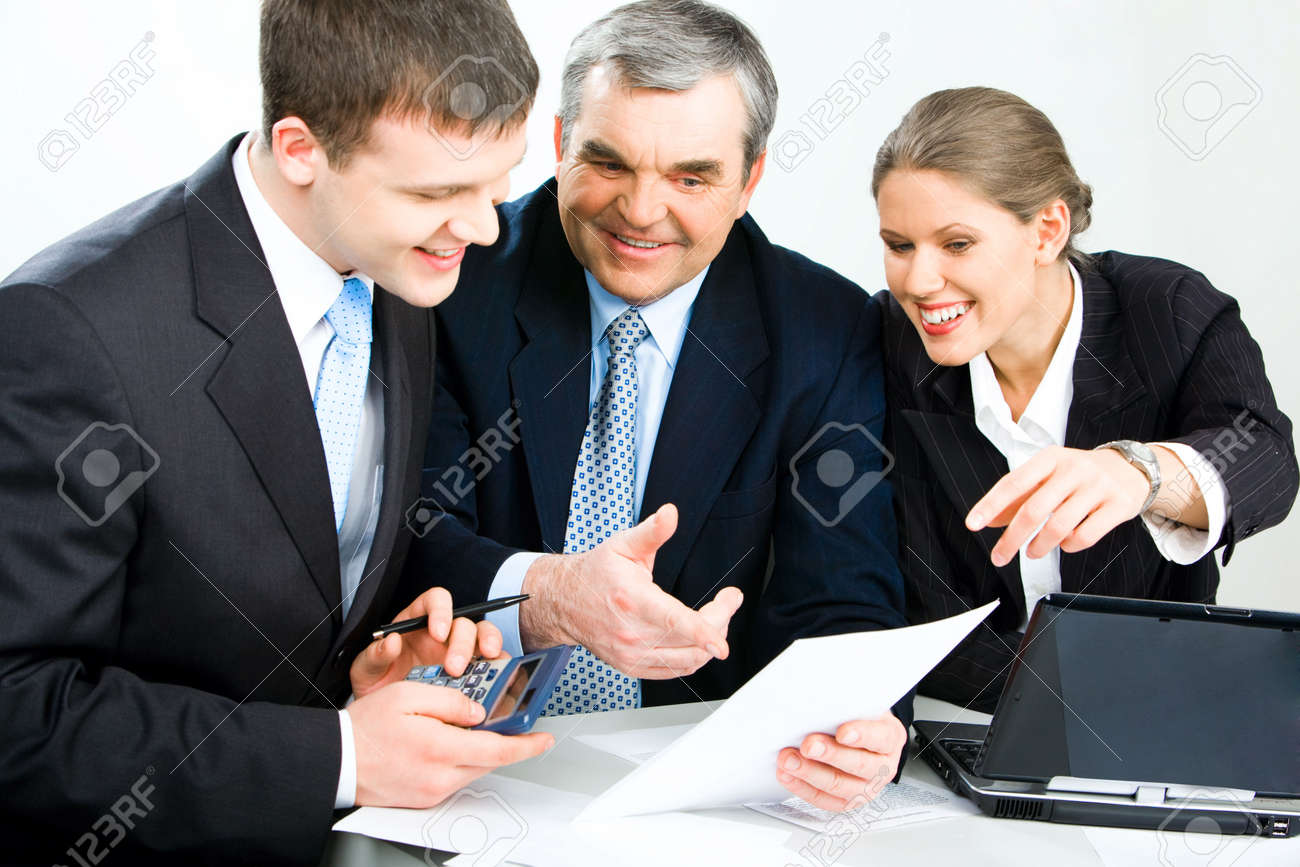 Photo of three colleagues working with papers and looking into one document with a laptop near by Stock Photo - 2836816