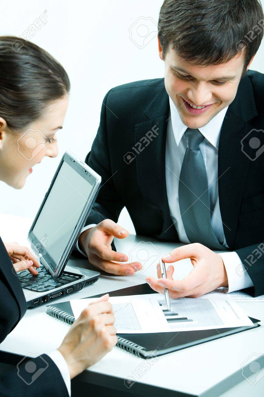 stock photo vertical image of two business partners looking at document at meeting and discussing it