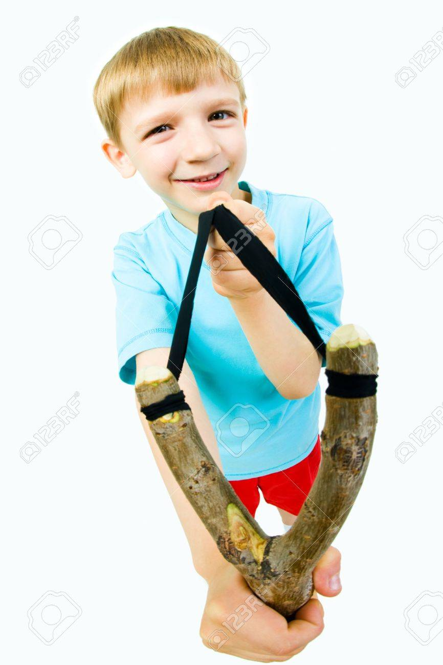 Portrait of playful boy with slingshot ready to catapult over white background Stock Photo - 3103301