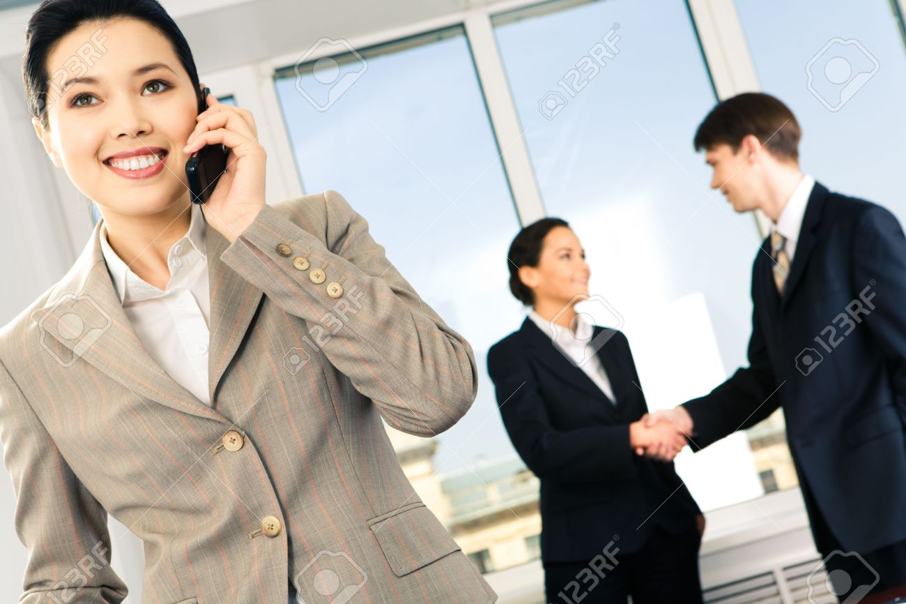 Portrait of happy woman calling on the phone on the background of business people�s handshake Stock Photo - 3146205