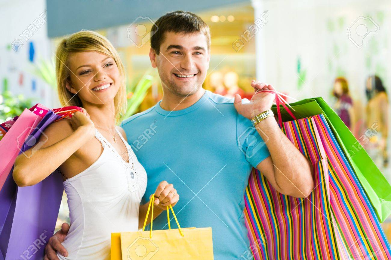 Happy man with paperbags in hand touching his girlfriend while in the shopping mall Stock Photo - 3246294