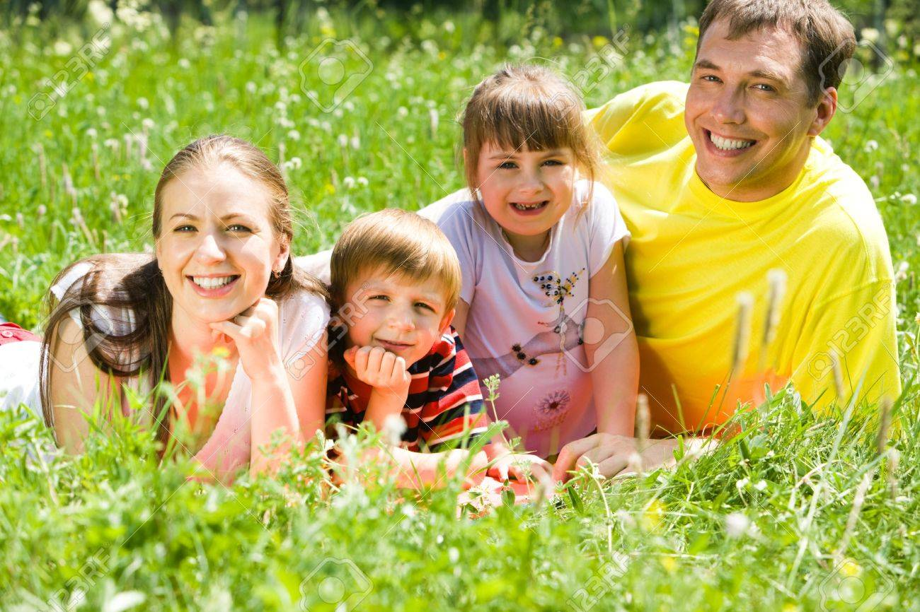 Portrait of family lying on grass in the park in summer and enjoying themselves Stock Photo - 3248873