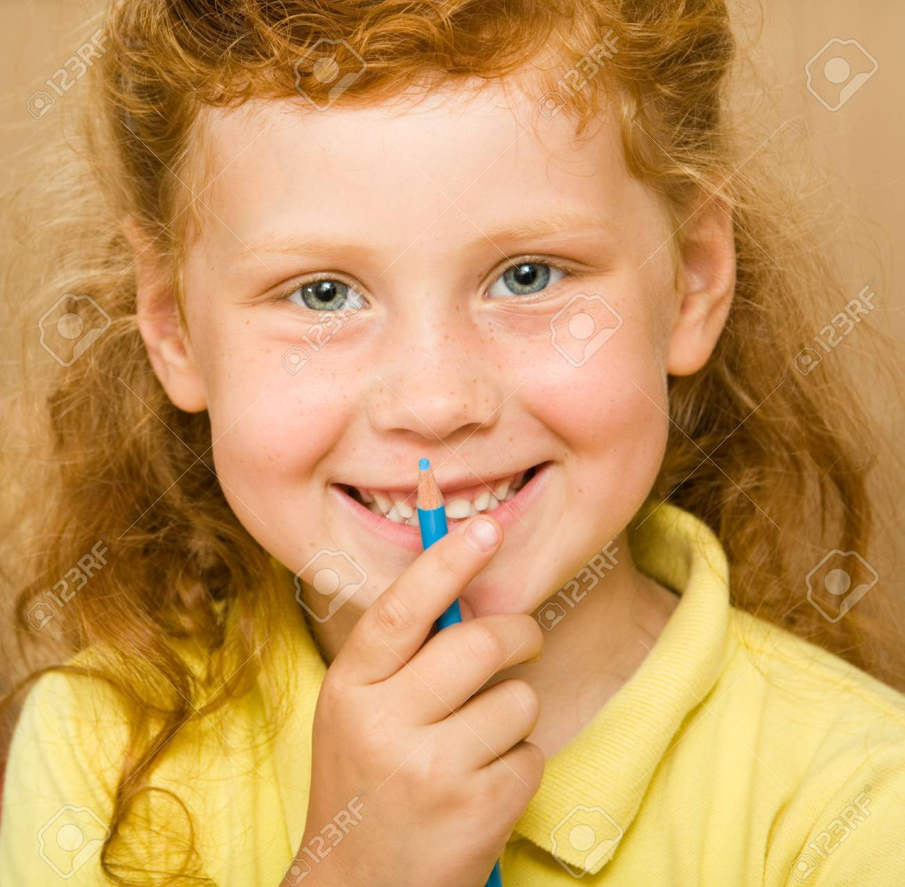 Face of red-headed girl holding blue pencil by her mouth looking at camera with smile Stock Photo - 3382723
