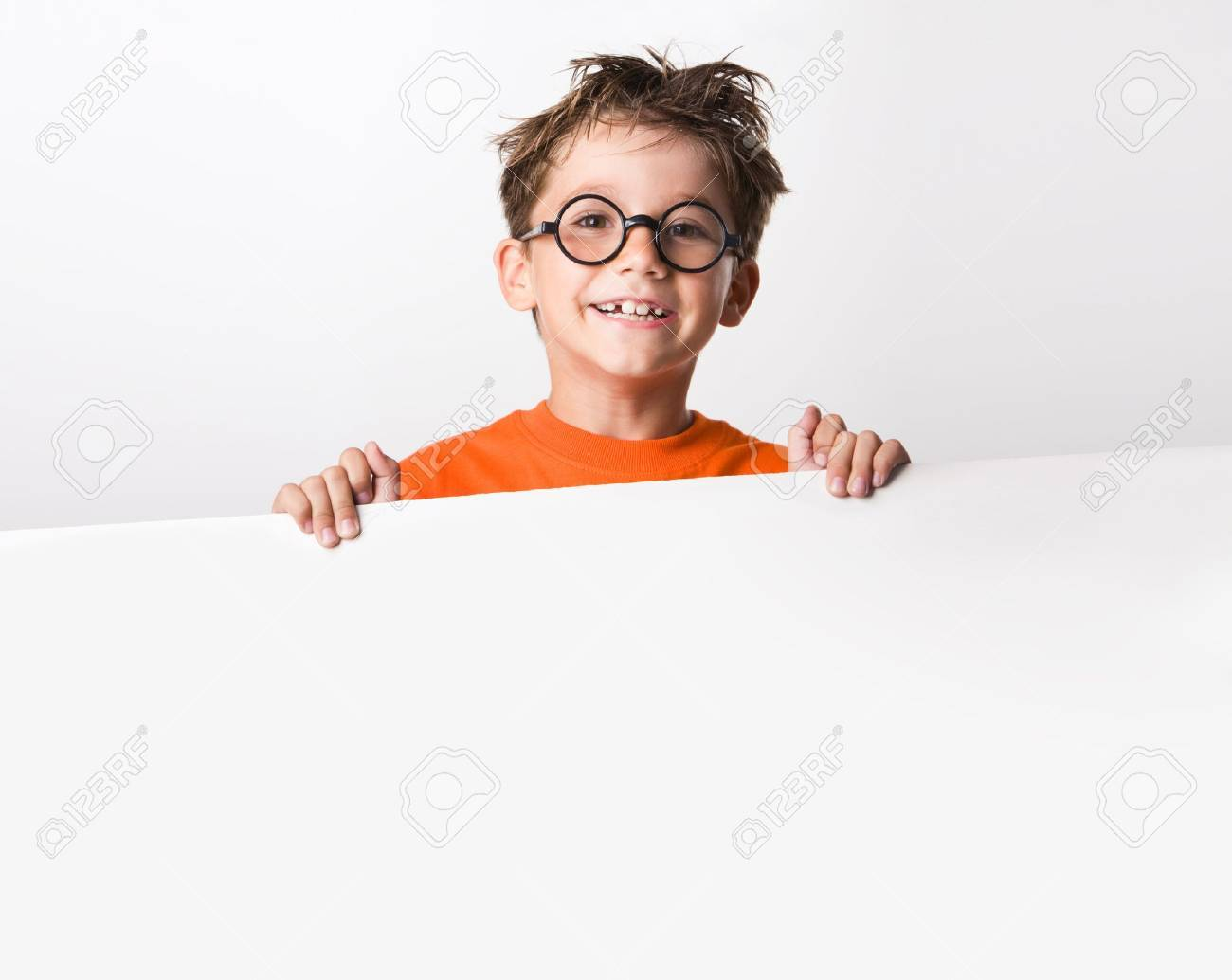 Image of joyful guy in glasses holding white partition and looking at camera with smile Stock Photo - 3556574