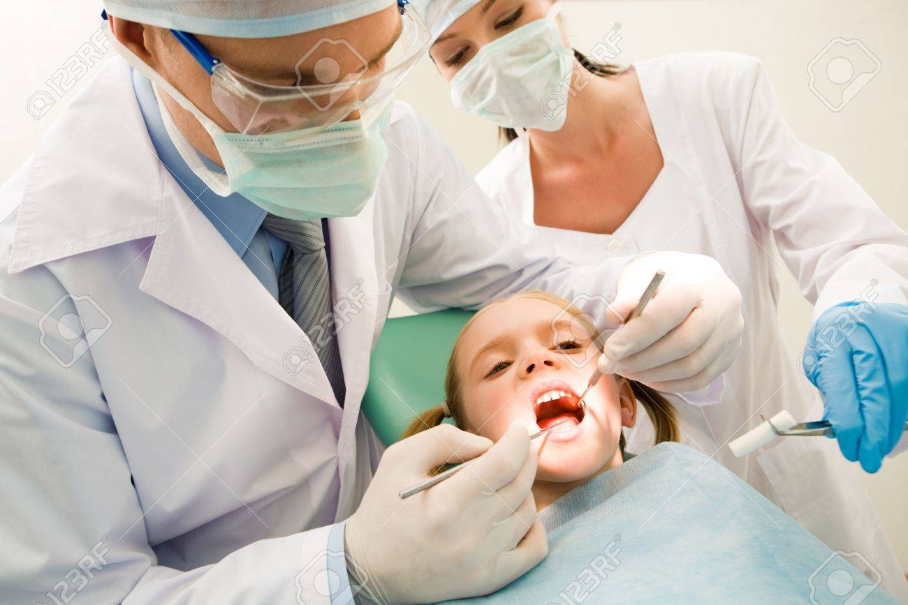 Image of dental checkup being given to little girl by dentist with assistant near by Stock Photo - 3709052