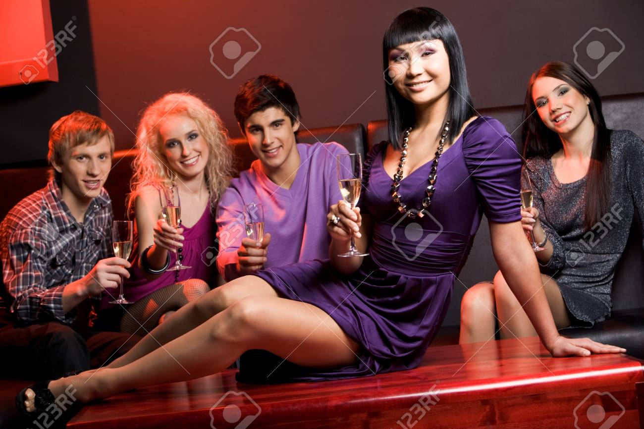 Image of glamorous woman with champagne sitting on table on background of her friends Stock Photo - 3997603