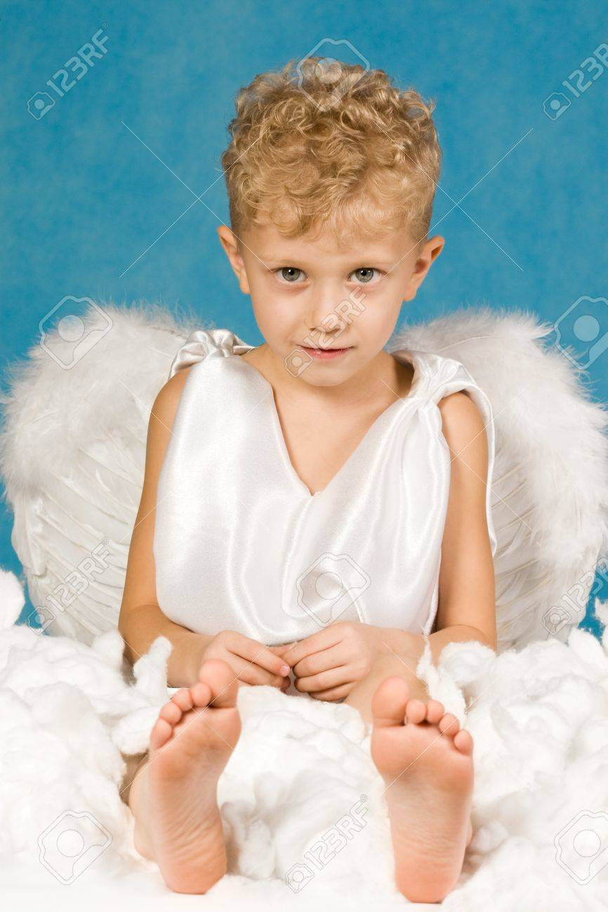 portrait of cute boy in angel clothes sitting in cloud and looking
