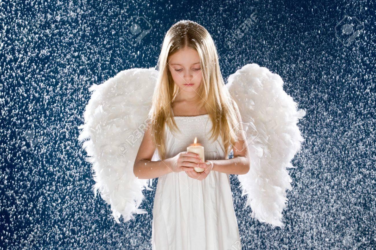 Photo of sad angel holding burning candle while standing under snowfall Stock Photo - 4113765