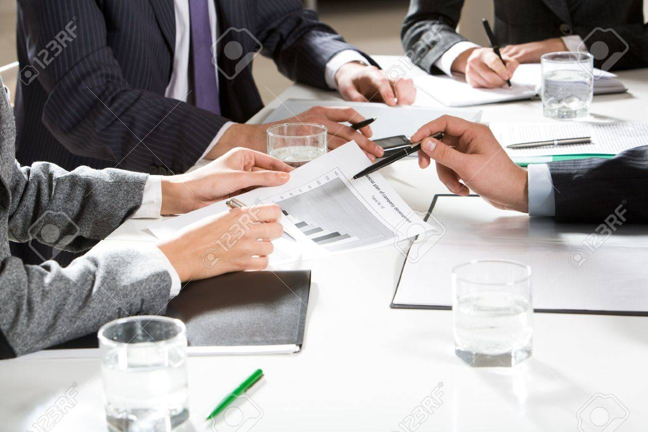 Human hands holding pens and papers, making notes in documents, touching the phone during business meeting Stock Photo - 4261137