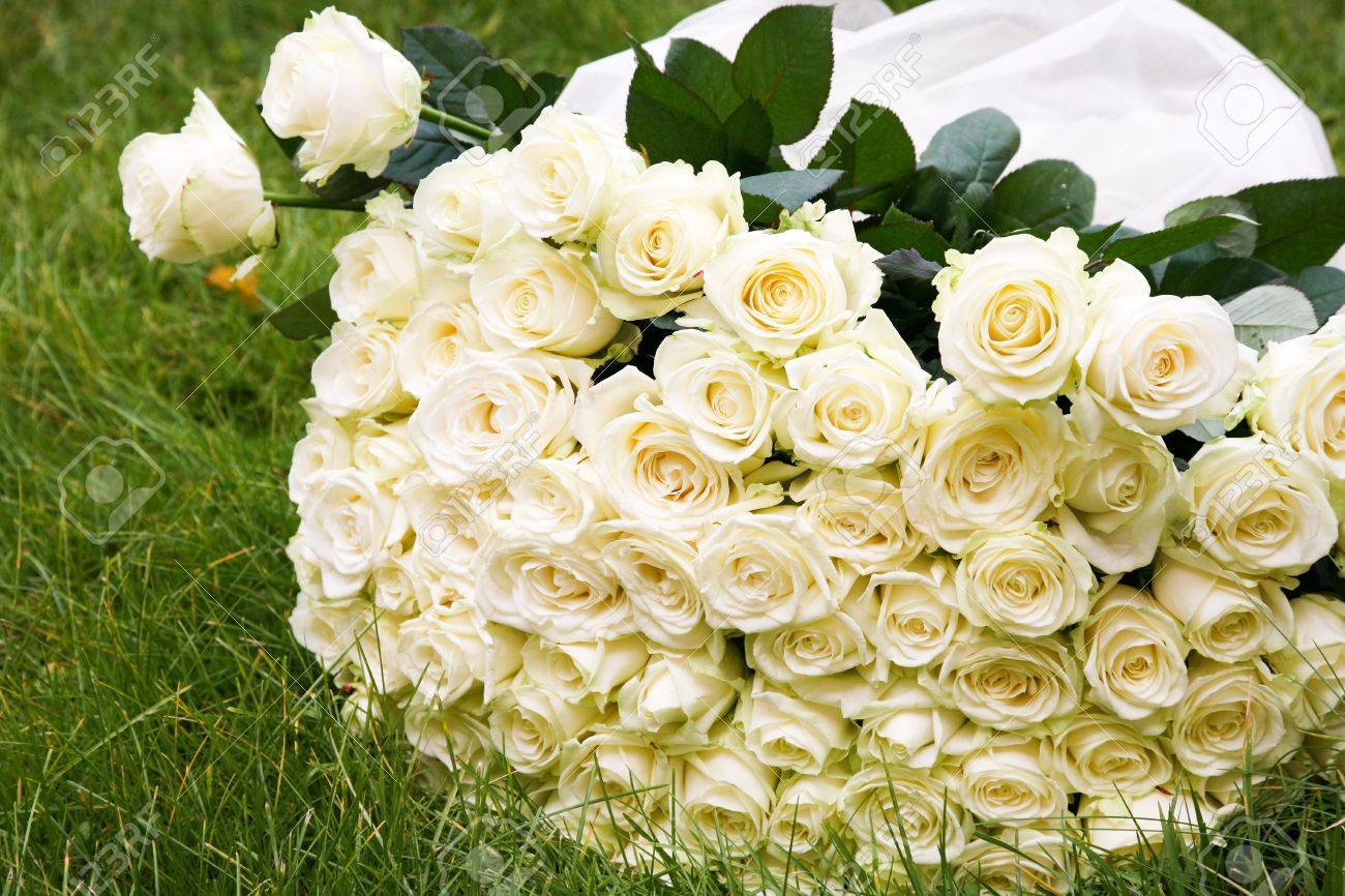 close up of big white rose bouquet made up of many flowers lying