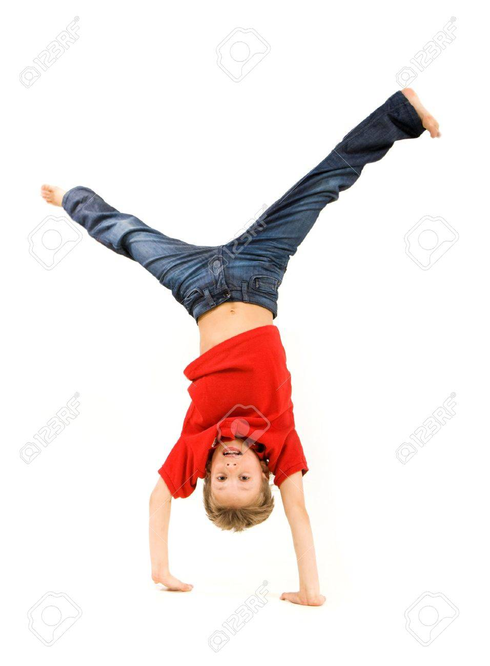 Playful lad standing on his arms with legs pointing upwards over white background Stock Photo - 4623370