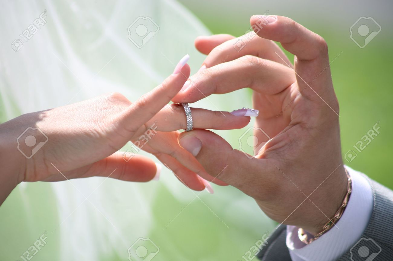 Close-up of groom�s hand putting wedding ring on bride�s finger Stock Photo - 4646987